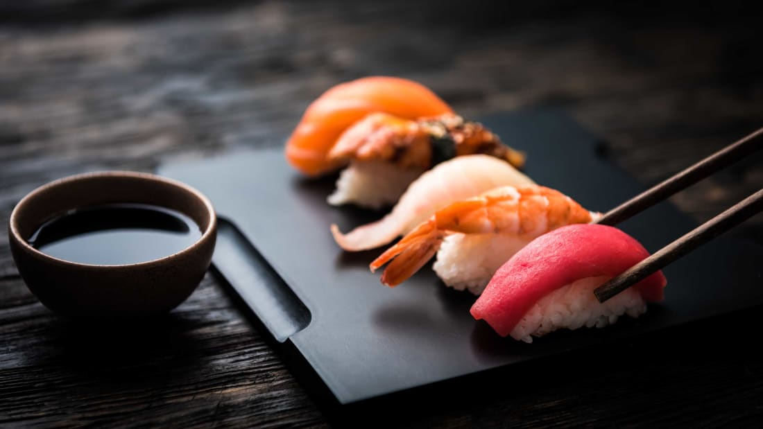 close up of sushi set with chopsticks and soy on black background