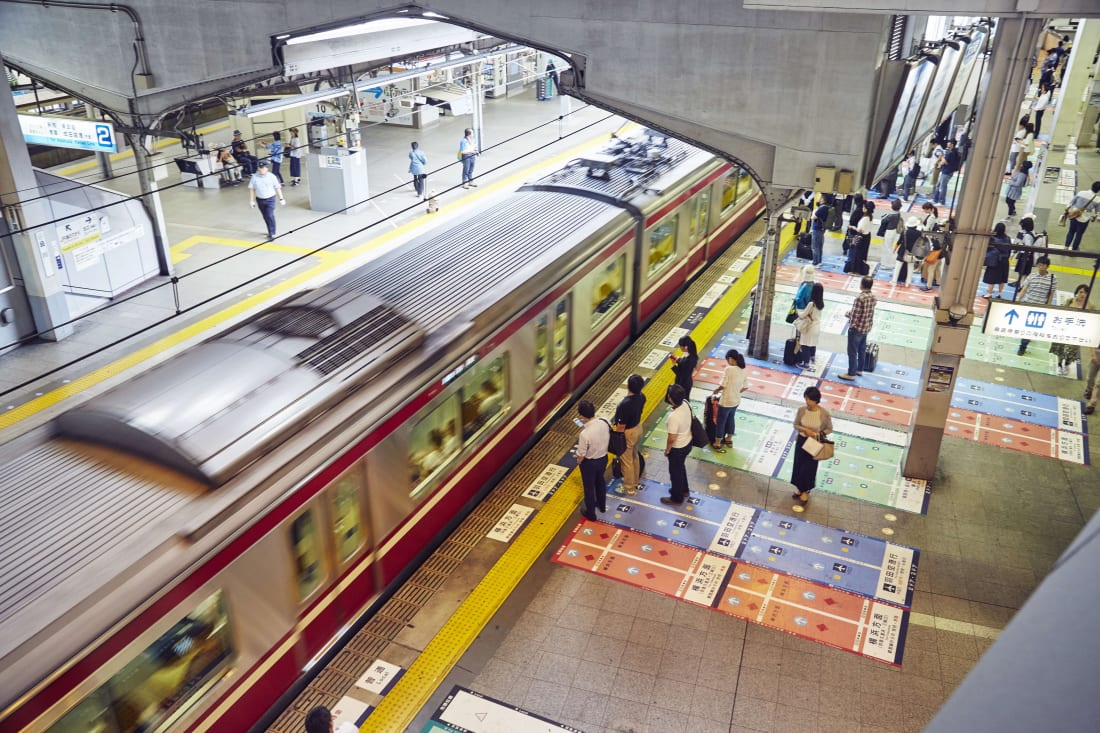 Commuters line up on color coded platforms at Shinagawa station, Tokyo.