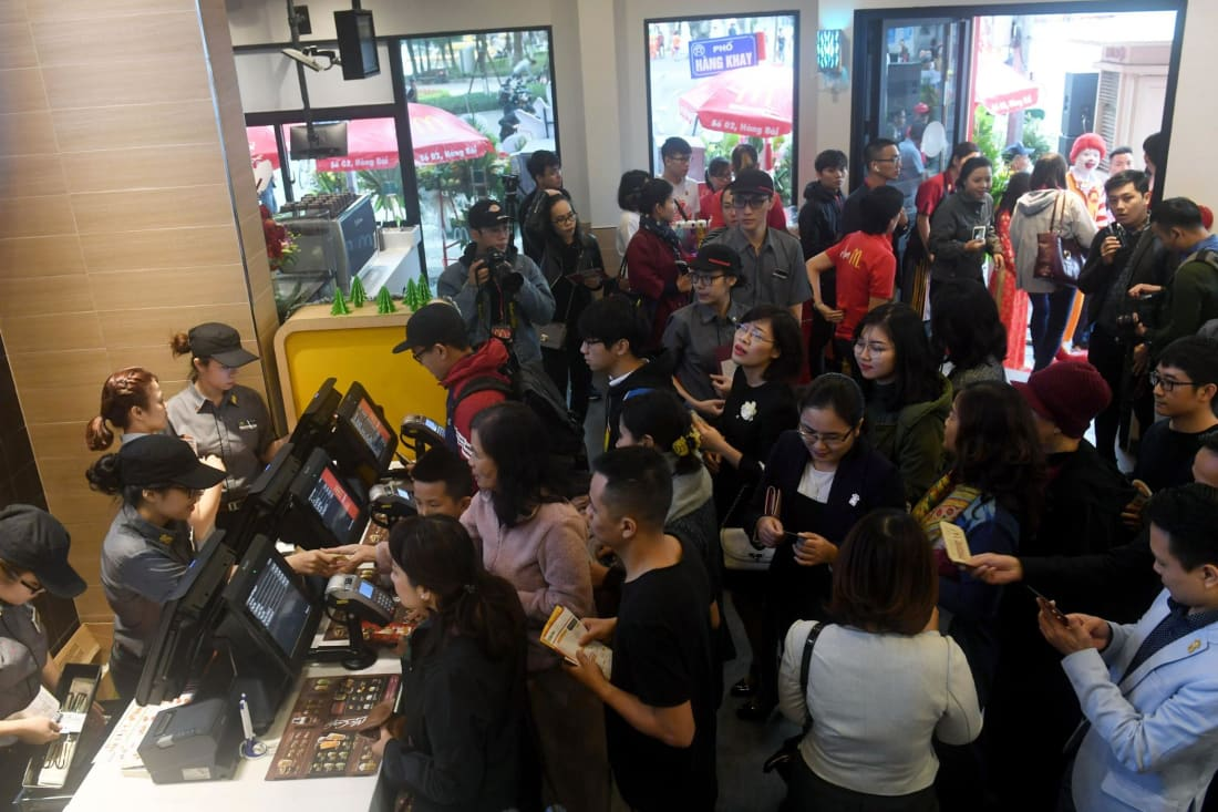 People queue up on the opening day of the first McDonald's fast food chain restaurant in Hanoi, Vietnam.