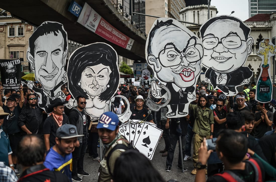 Activists hold up caricatures of Najib Razak and Rosmah Mansor (center). Political art became a key tool of protest in Malaysia during Najib's rule.