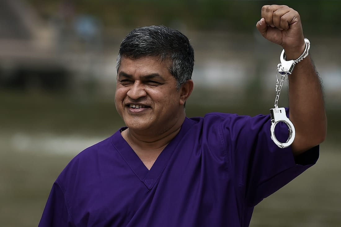Malaysian cartoonist Zulkifli Anwar Ulhaque, popularly known as Zunar, poses with handcuffs prior to a book-launch event in Kuala Lumpur on February 14, 2015.