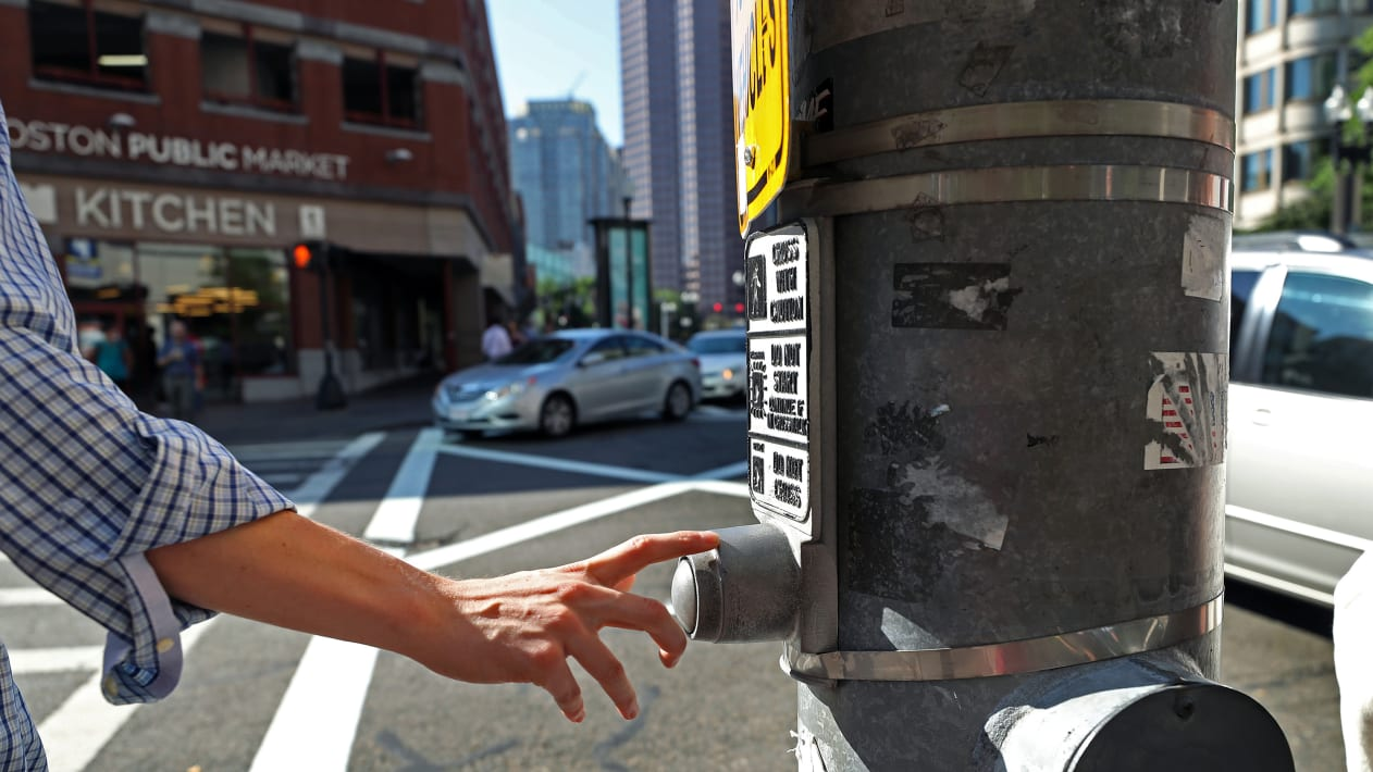 BOSTON, MA - JULY 21: A pedestrian presses a traffic signal button at Congress and Sudbury Streets in Boston on Jul. 21, 2017. The vast majority of these buttons that dot downtown neighborhoods don't actually do anything. Thats by design. Officials say the citys core is just too congested  with cars and pedestrians  to allow any one person to manipulate the cycle. (Photo by David L. Ryan/The Boston Globe via Getty Images)
