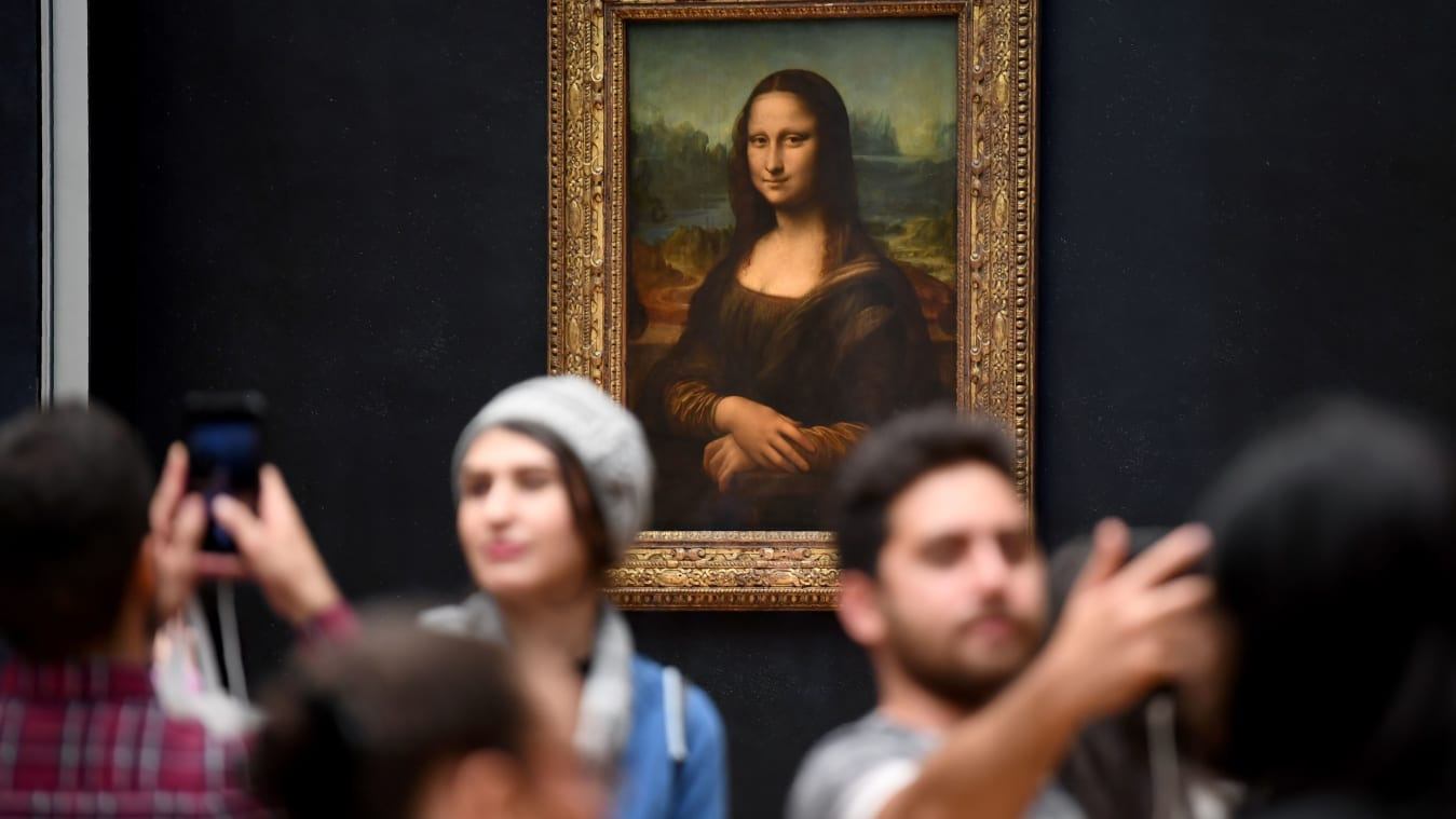 "Visitors take pictures in frront of Mona Lisa after it was returned at its place at the Louvre Museum in Paris on October 7, 2019. - Leonardo da Vinci's masterpiece, the ""Mona Lisa,"" returned to her usual spot in Paris' Louvre Museum on October 7 following a two-month renovation for the gallery housing the world's most famous painting. (Photo by ERIC FEFERBERG / AFP) (Photo by ERIC FEFERBERG/AFP via Getty Images)"