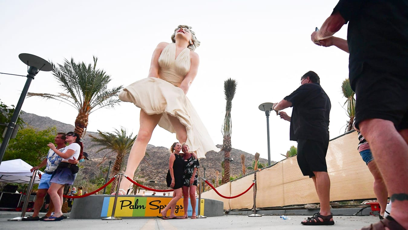 """People visit the """"Forever Marilyn"""" statue unveiled today on its return to Palm Springs, California on June 20, 2021. - The 26-foot tall and 17-ton sculpture by artist Seward Johnson Atelier was displayed earlier this decade in Palm Springs, but the return has drawn the ire of residents on infringement of surrounding natural landscape views and on allegations the statue is sexist and innapropriate, despite the popularity of Marilyn Monroe's iconic dress-flying pose from the 1955 comedy """"The Seevn Year Itch."""" - RESTRICTED TO EDITORIAL USE - MANDATORY MENTION OF THE ARTIST UPON PUBLICATION - TO ILLUSTRATE THE EVENT AS SPECIFIED IN THE CAPTION (Photo by Frederic J. BROWN / AFP) / RESTRICTED TO EDITORIAL USE - MANDATORY MENTION OF THE ARTIST UPON PUBLICATION - TO ILLUSTRATE THE EVENT AS SPECIFIED IN THE CAPTION / RESTRICTED TO EDITORIAL USE - MANDATORY MENTION OF THE ARTIST UPON PUBLICATION - TO ILLUSTRATE THE EVENT AS SPECIFIED IN THE CAPTION (Photo by FREDERIC J. BROWN/AFP via Getty Images)"""