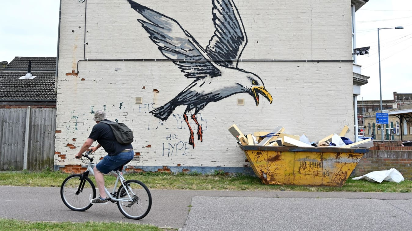 A cyclist rides past a stensil of a gull about to swoop down onto a carton of chips, the subject of a graffiti artwork bearing the hallmarks of street artist Banksy on a wall in Lowestoft on the East Coast of England on August 8, 2021.