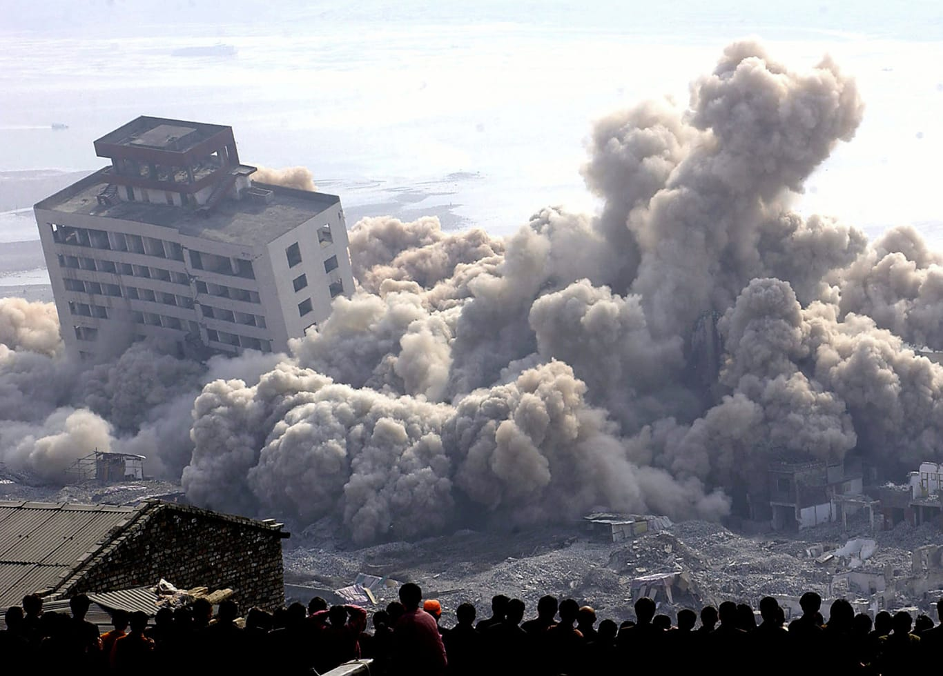 Residents of Fengjie, in southwest China's Chongqing, watch the demolition of buildings in their town on November 4, 2002, to make room for the Three Gorges Dam's resevoir.