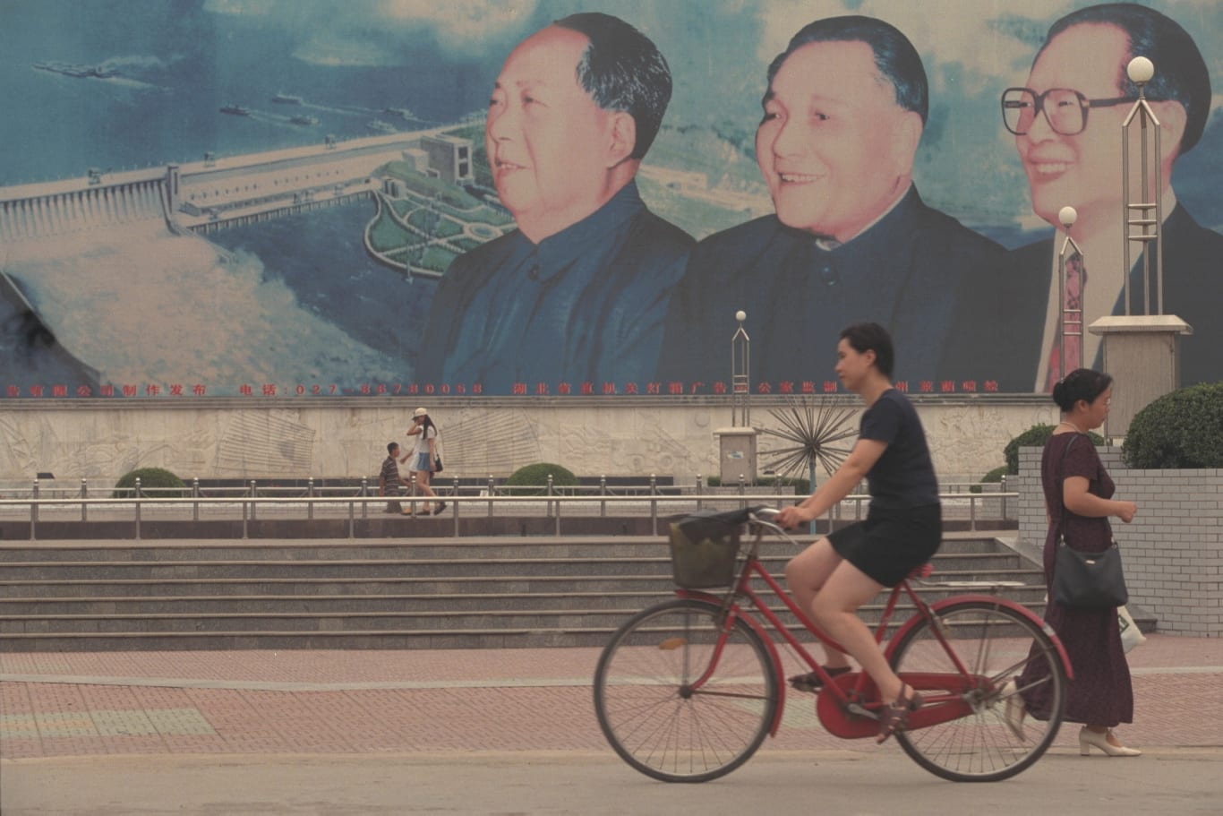 The faces of Chinese leaders Mao Zedong, Deng Xiaoping and Jiang Zemin appear on a large mural of the Three Gorges Dam in Wuhan.