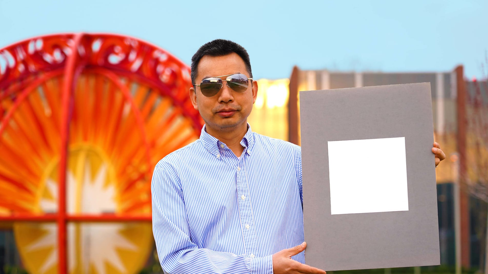 Xiulin Ruan, a Purdue University professor of mechanical engineering, poses with a sample of the new, sunlight reflecting paint.