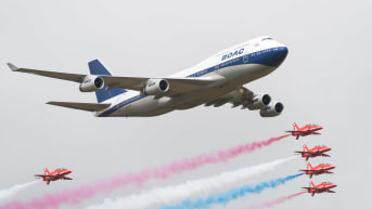 A special liveried Boeing 747 takes to the skies alongside the Red Arrows during the 2019 Royal International Air Tattoo on July 20, 2019.