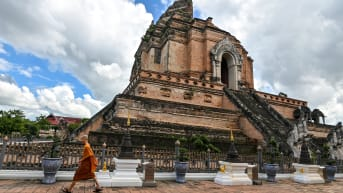 A novice monk walks past Wat Chedi Luang Buddhist temple in Chiang Mai on October 31, 2020.