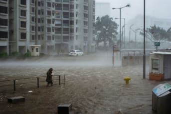 A man wades across the flood in Heng Fa Chuen during the approach of super Typhoon Mangkhut to Hong Kong on September 16, 2018.