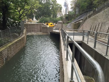 One of the tunnel's intakes, full of rainwater. The water progresses from the intake into the tunnel, instead of inundating the city below. The entrance to the tunnel lies near the middle of the photo, under the life preserver ring.