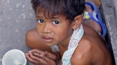 A Thai Boy Begs For Money Along Streetside Pavement In Bangkok