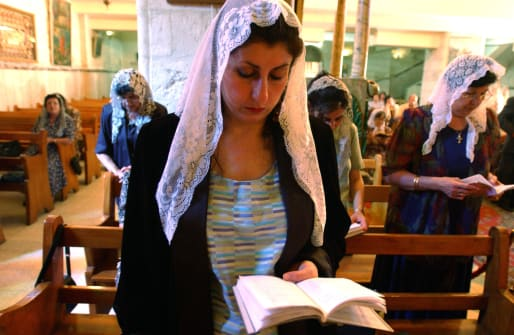 A Greek Orthodox Christian woman attends Friday mass service in the West Bank town of Ramallah, Palestine, wearing a lace veil.