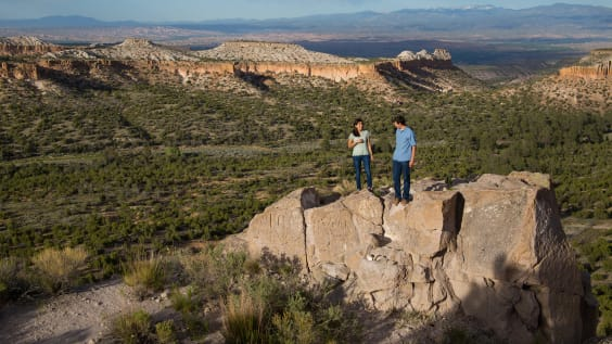Two hikers stand in a mountain valley in Los Alamos County, New Mexico.