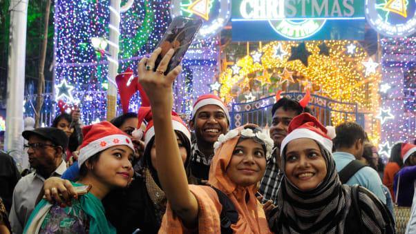Un gruppo di giovani fa un selfie durante le celebrazioni della vigilia di Natale in Park Street a Calcutta.