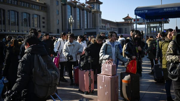 Travellers wait for their trains outside the entrance to Beijing railway station in the Chinese capital on January 10, 2020.