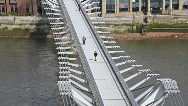 Pedestrians cross a quiet Millennium Footbridge across the River Thames in London on March 17.