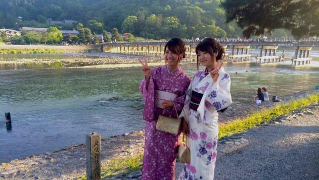 Kimono-clad Japanese tourists pose in front of Arashiyama's Togetsukyo Bridge.