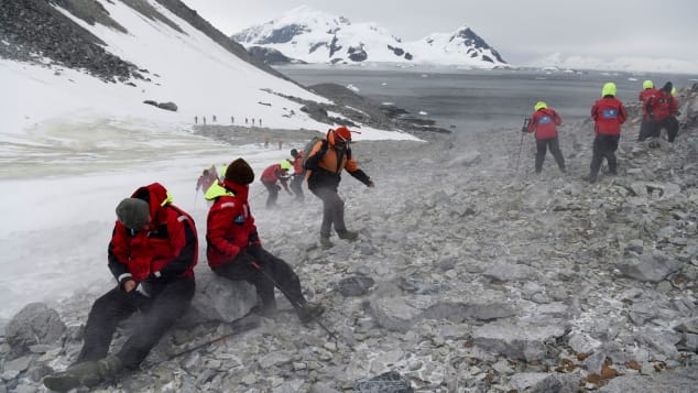 Tourists struggle to climb up a hill in Orne Harbour, Antarctic, on March 05, 2016