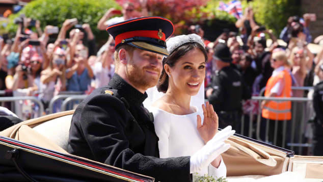 Harry and Meghan ride in an open carriage on their wedding day.