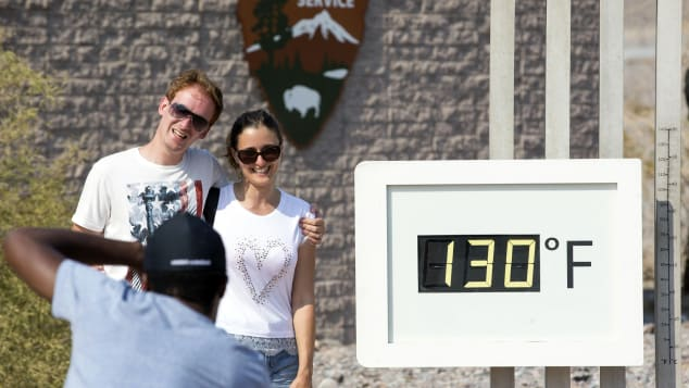 A couple poses at the Furnace Creek Visitor Center thermometer in Death Valley National Park on July 26, 2018.