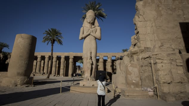 A visitor takes a photo of a Ramses II statue at the entrance of Karnak Temple.