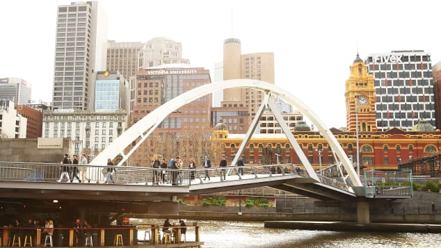Melbourne's neighborhoods are a big selling point. Here, people cross a pedestrian bridge in popular Southbank.