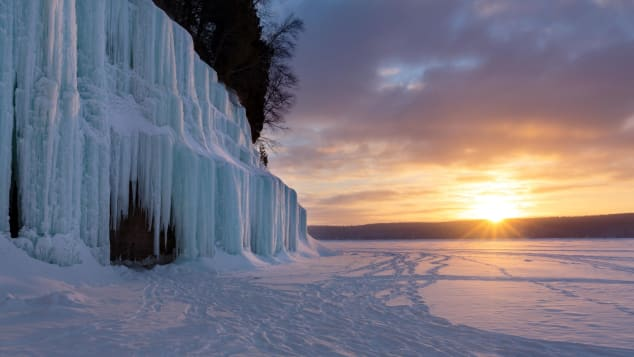 Sunrise over a frozen Lake Superior, with Grand Island's ice curtains in the foreground.