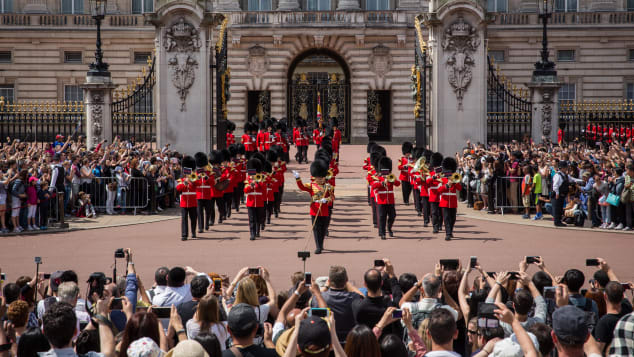 Tourists watch the Changing of the Guard at Buckingham Palace.