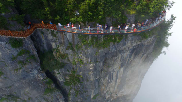 Tourists take on the Coiling Dragon Cliff skywalk in Zhangjiajie National Forest Park.