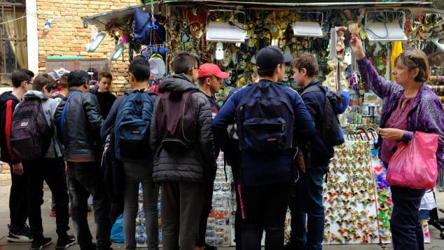 A teacher rounds up her students in front of a kiosk selling knick knacks.