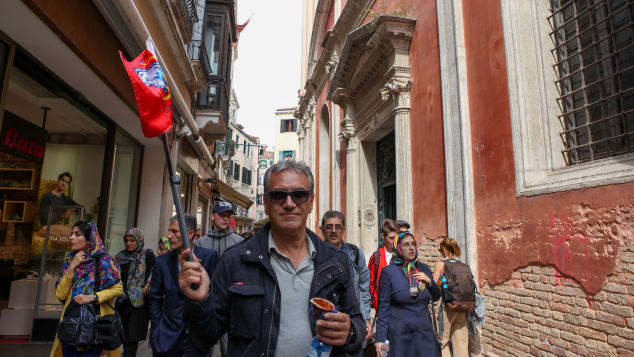 A tour guide leads his group through Venice's winding streets.