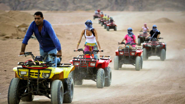 Tourists ride quad-bikes during part of a desert safari trip in Egypt.