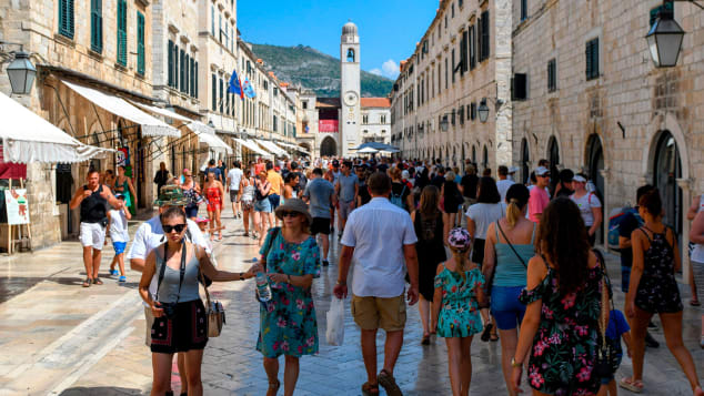 Tourists stroll in a street as they visit the centre of Dubrovnik