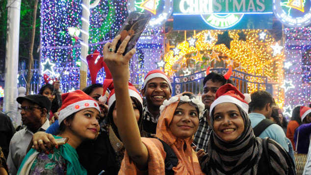 A group of young people takes a selfie during Christmas Eve celebrations  on Park Street in Kolkata.