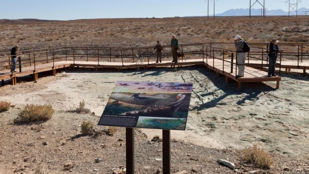Visitors to the Mill Canyon dinosaur track site can walk along an elevated boardwalk above Early Cretaceous-era tracks and contemplate illustrations such as this one by artist Brian Engh.