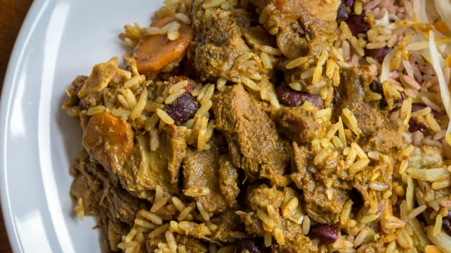 A plate of Jamaican curried goat, served with traditional rice and peas.