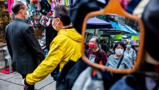 People wearing face masks walk through a Hong Kong market on February 25, 2020.
