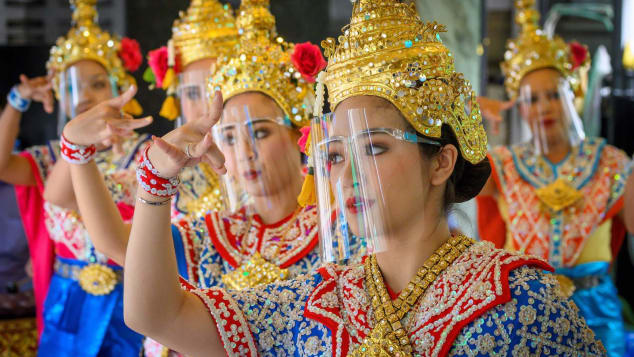 Traditional Thai dancers wearing protective face shields perform at Bangkok's Erawan Shrine, which was reopened after the Thai government relaxed measures to combat the spread of Covid-19 on May 4.