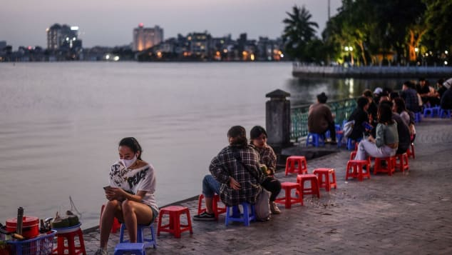 A woman sits by the lake at sunset in Hanoi on May 2.