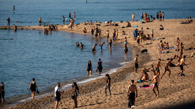 People enjoy the beach in Barcelona, Spain, Wednesday, May 20, 2020. Barcelona allowed people to walk on its beaches Wednesday, for the first time since the start of the coronavirus lockdown over two months ago.