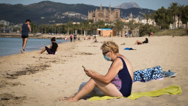 A woman wearing a face mask sits at the Can Pere Antoni Beach in Palma de Mallorca on May 25, 2020