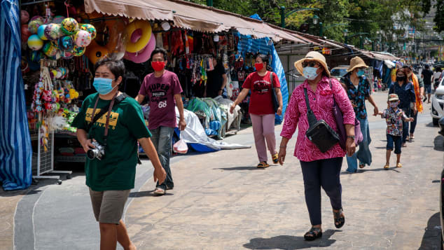 Visitors wearing face masks, amid concerns over the spread of the COVID-19 coronavirus, walk along street shops in Hua Hin beach in Thailand on May 19, 2020
