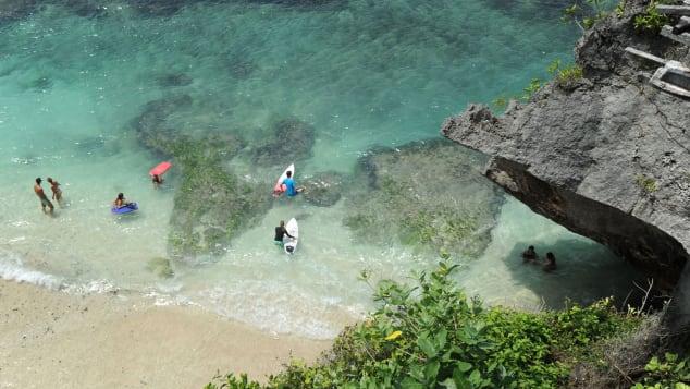 Tourists prepare to surf at Uluwatu beach South Kuta in Badung regency on Bali island, on December 20, 2018