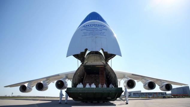 """Члены экипажа в защитных костюмах стоят внутри грузового самолета Ан-225 """"Мрия"""" во время доставки защитных масок из Китая."""