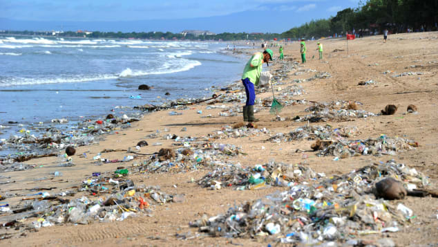This photo taken on December 19, 2017 shows rubbish collectors clearing trash on Kuta beach near Denpasar, on Indonesia's tourist island of Bali.