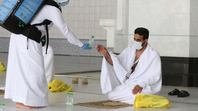 A picture taken on July 29, 2020 shows a pilgrim receiving water at the Grand Mosque complex in the holy city of Mecca.