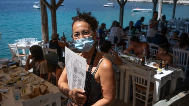 Waitress Vasiliki Besiou wears a face mask while waiting tables at the Takis Taverna in the pretty coastal village of Limeni.