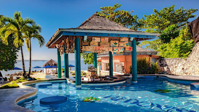 The nude pool, with a swim-up bar, is a central gathering spot for resort guests.
